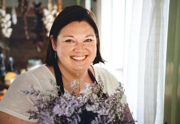 Florist, der einen blumenstrauß von caspia-blumen hält