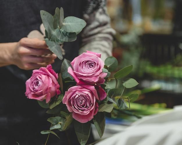 Florist, der einen blumenstrauß von den rosa rosen macht