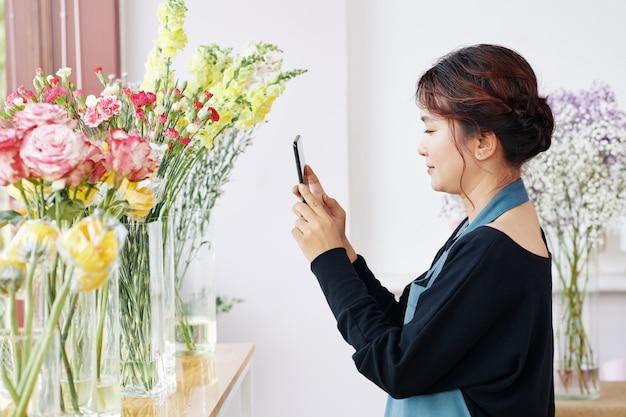 Florist, der fotos von blumen für soziale medien macht