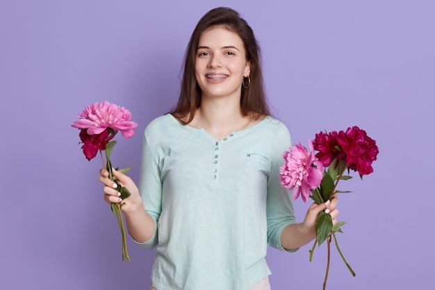 Florist der jungen frau, der blumenstrauß mit blumen macht und pfingstrosen in den händen hält