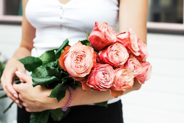 Florist der jungen frau, der blumenstrauß von rosa rosen an der straße hält