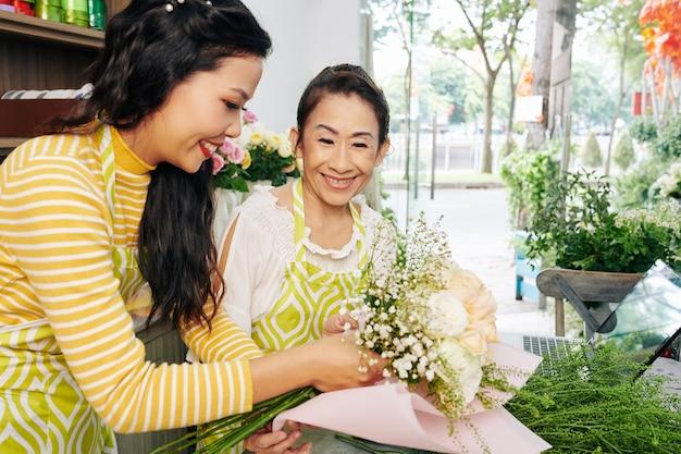 Florist, der mitarbeiter hilft, blumenstrauß in hellrosa papier zu wickeln