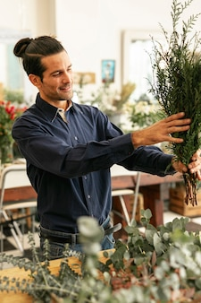 Florist, der pflanzen mittlerer schuss anordnet