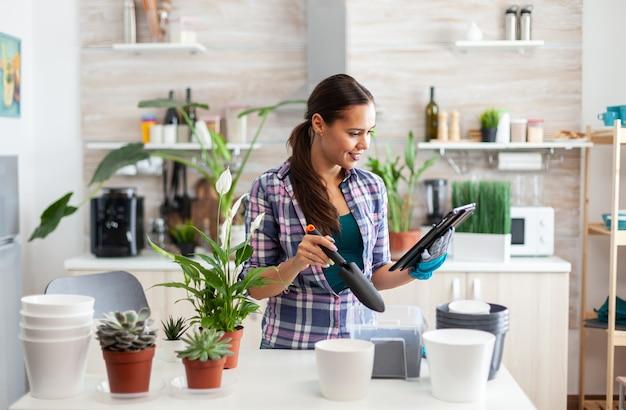 Florist, der während der gartenarbeit neue blumen in der heimischen küche aussät