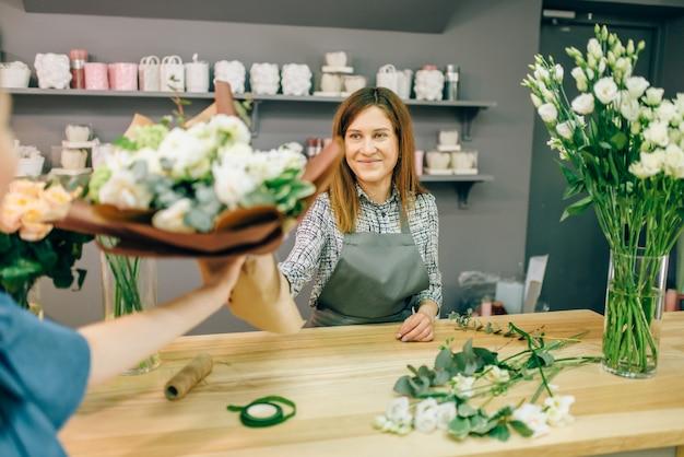 Florist gibt weiblichen kunden in der blumenboutique ein frisches bouquet.