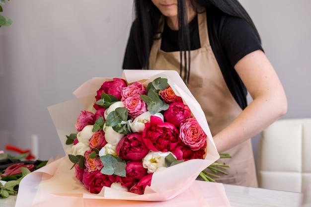Florist in schwarzen handschuhen kreiert einen strauß roter pfingstrosen