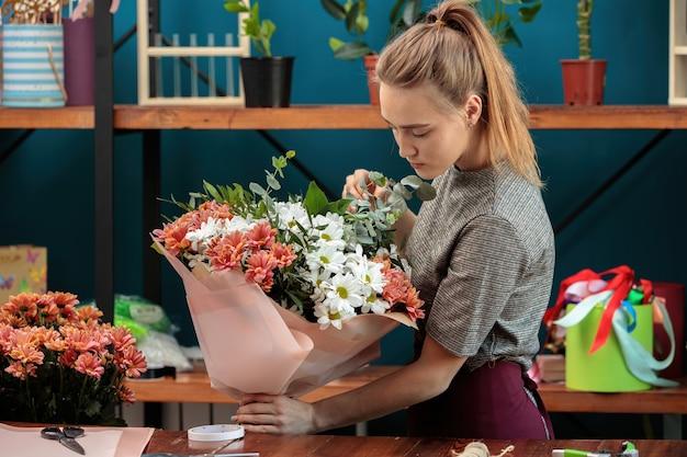 Florist macht einen blumenstrauß. ein junges erwachsenes mädchen hält einen großen strauß mehrfarbiger chrysanthemen in den händen und überprüft ihn.