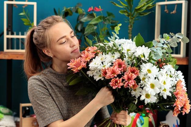 Florist macht einen blumenstrauß. ein junges erwachsenes mädchen hält einen großen strauß mehrfarbiger chrysanthemen in den händen
