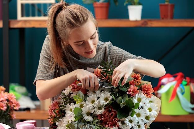 Florist macht einen blumenstrauß. ein junges erwachsenes mädchen schneidet blumen in einem strauß mehrfarbiger chrysanthemen mit einer gartenschere.