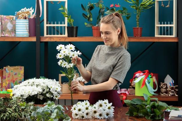 Florist macht einen blumenstrauß. ein junges erwachsenes mädchen wählt weiße chrysanthemen für einen blumenstrauß.