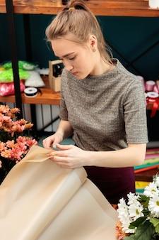 Florist macht einen blumenstrauß. junges erwachsenes mädchen wählt papier für dekoration.