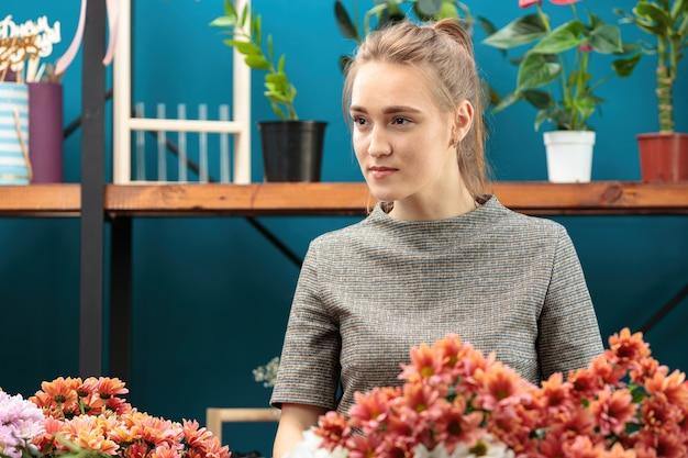 Florist macht einen strauß aus bunten chrysanthemen. ein junges erwachsenes mädchen schaut zur seite.