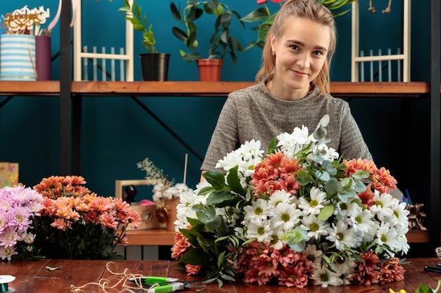 Florist macht einen strauß aus bunten chrysanthemen.