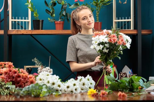 Florist macht einen strauß aus bunten chrysanthemen