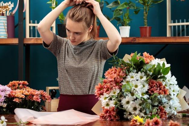 Florist macht einen strauß chrysanthemen. ein junges erwachsenes mädchen glättet ihre haare auf dem kopf.