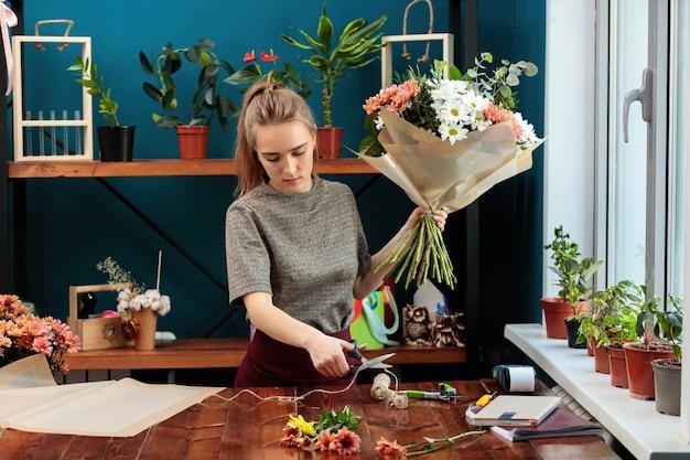 Florist macht einen strauß. ein junges erwachsenes mädchen hält einen großen strauß bunter chrysanthemen in den händen und schneidet mit einer schere einen faden zum binden ab.