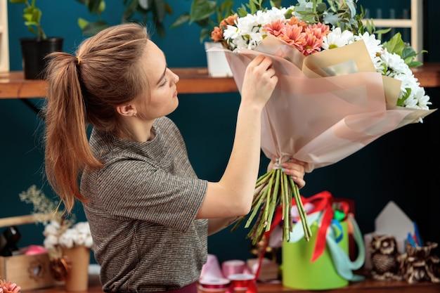 Florist macht einen strauß. ein junges erwachsenes mädchen hält einen großen strauß bunter chrysanthemen in den händen und überprüft ihn.