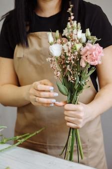 Florist mädchen in sandschürze bei der arbeit erstellt einen blumenstrauß mit eustomas