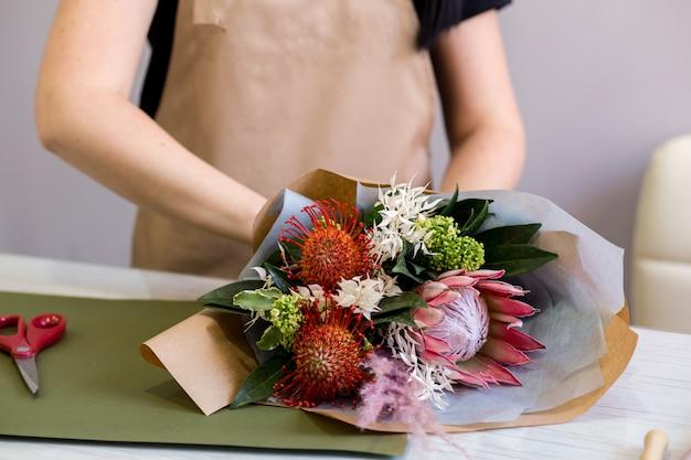 Florist mädchen in sandschürze bei der arbeit schafft einen strauß proteas
