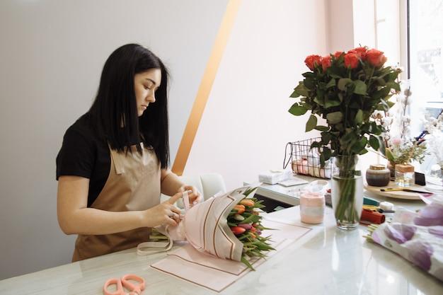 Florist mädchen schafft einen strauß tulpen in einem blumenladen