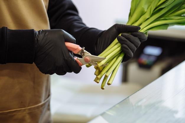 Florist mädchen schneidet die spitzen der weißen tulpen in einem blumenladen