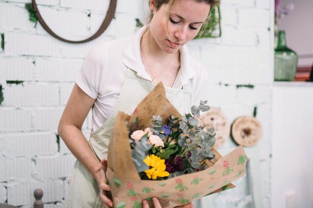 Florist mit eingewickeltem blumenstrauß