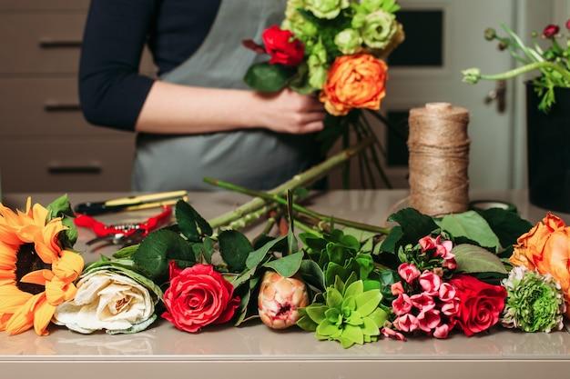 Florist mit rosenstrauß bei der arbeit.