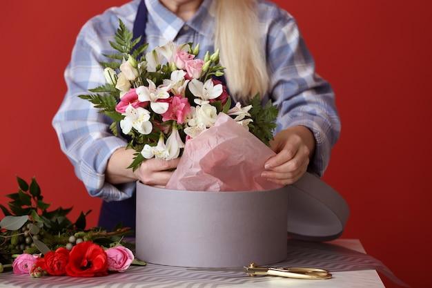 Florist mit schönem blumenstrauß und geschenkbox am tisch, nahaufnahme