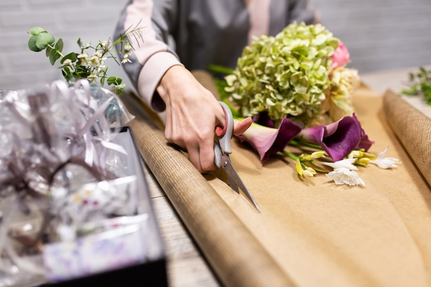 Florist schneidet geschenkpapier für einen blumenstrauß.