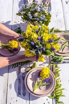 Floristen schmücken mit blumensträußen aus gelben schwertlilien eine hochzeit im rustikalen stil.