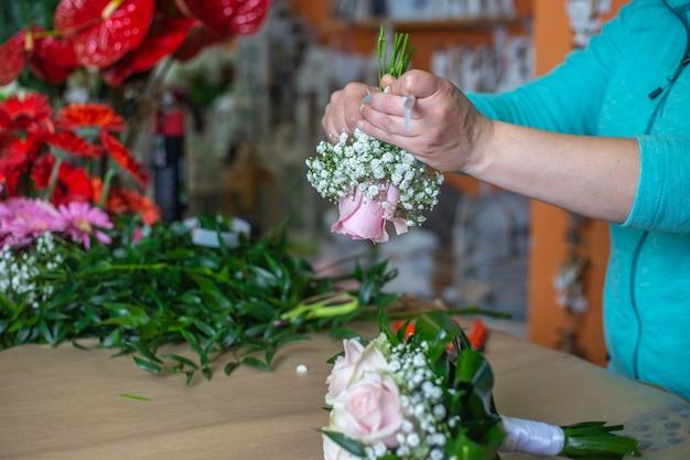 Floristenfrau bindet einen blumenstrauß mit rosen in einem blumenladen