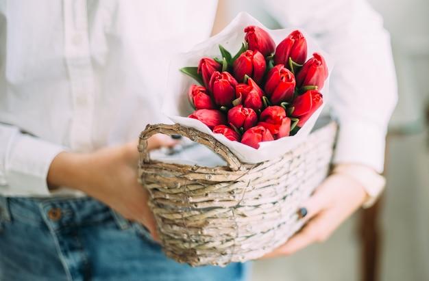 Floristenfrau, die einen korb mit roten tulpen im weißen papier hält.