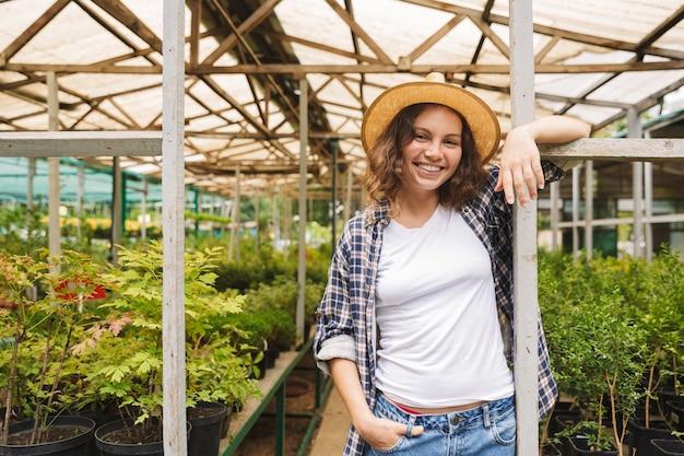 Floristenfrau, die im gewächshaus über pflanzen arbeitet