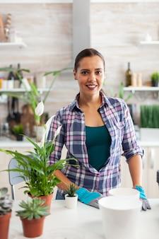Floristenfrau, die in die kamera schaut, während sie blumen in der küche für heimtextilien pflanzt