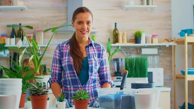 Floristenfrau, die kamera betrachtet und lächelt, umgeben von blumen. mit fruchtbarer erde mit einer schaufel, einem weißen keramiktopf und einer hausblume, pflanzen, die zum umpflanzen für die hausdekoration vorbereitet sind.