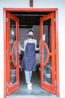 Floristenfrau, die schürze und gesichtsmaske trägt, die den türblumenladen offen steht