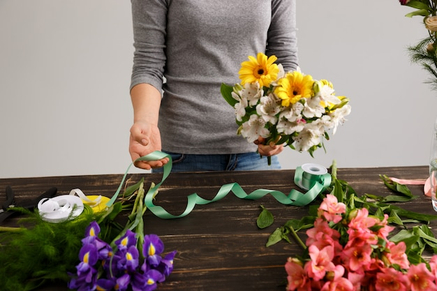 Floristenfrau machen blumenstrauß aus bunten blumen