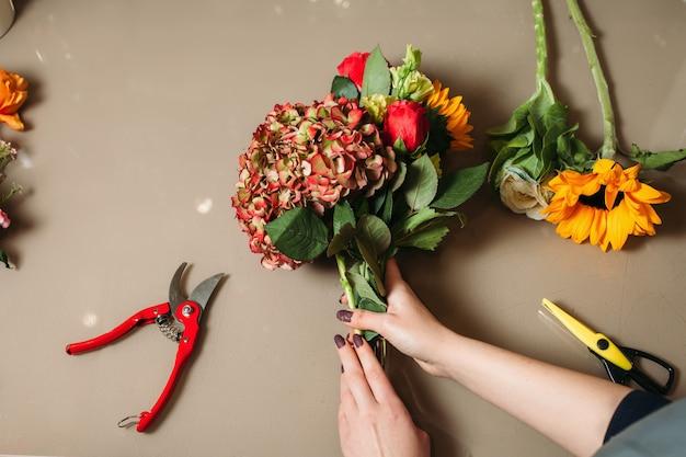 Floristenhände, die rose mit gartenschere schneiden