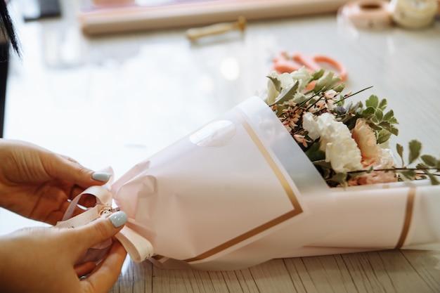 Floristenhände kreieren einen blumenstrauß in einem blumenladen