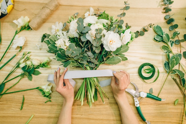 Floristenhände schneiden blumenkomposition mit gartenschere