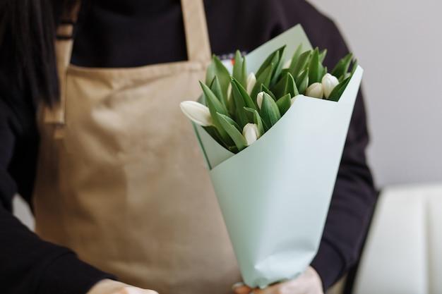 Floristenmädchen schafft einen strauß weißer tulpen in einem blumenladen