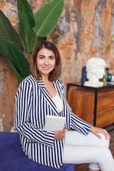 Floristenmanager oder designerfrau, die in ihrem büro mit buch sitzen.