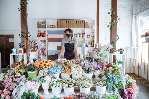 Floristenmann, der gesichtsmaske trägt, die hinter einem blumenstrauß im blumenladen steht