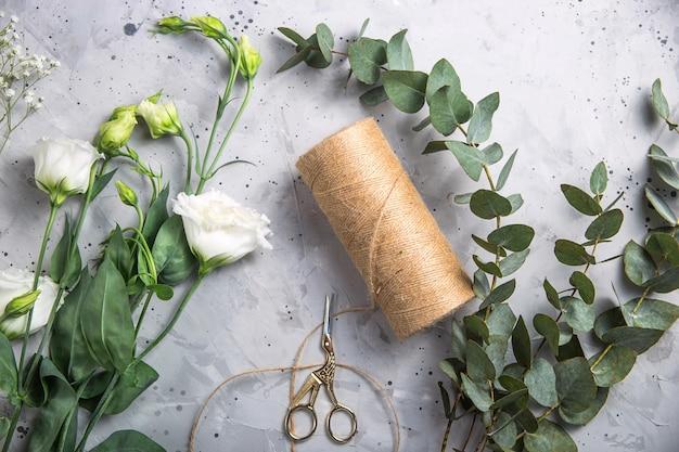 Floristenwerkzeuge und arbeitsplatz mit bändern, blumen und scheren
