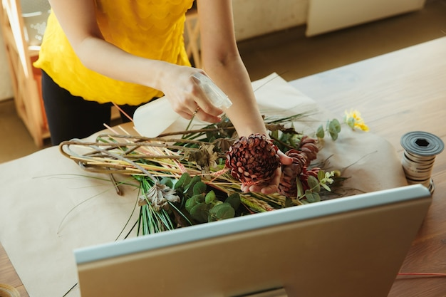 Floristin bei der arbeit frau zeigt, wie man blumenstrauß zu hause arbeitet, hautnah