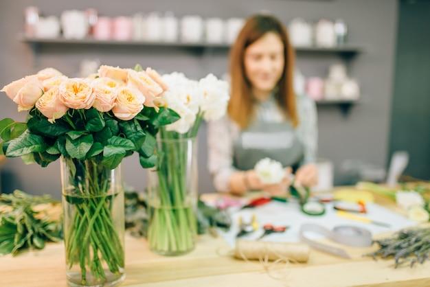Floristin bereitet rosenstrauß am arbeitsplatz vor