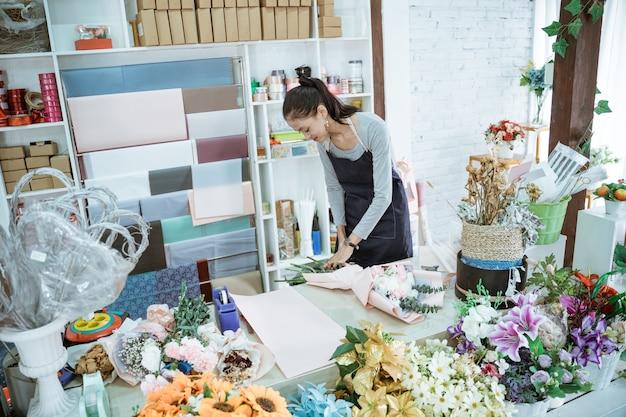 Floristin der jungen frau, die im blumenladen arbeitet, machen flanellblume in einem tischarbeitsbereich bestellen