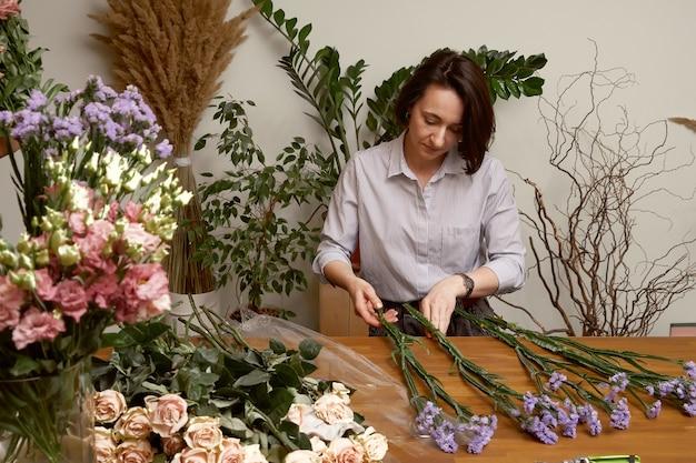Floristin der jungen frau in ihrem studio, das einen schönen blumenstrauß macht