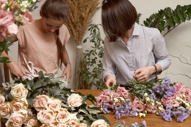 Floristin der jungen frauen in ihrem studio, das einen schönen blumenstrauß macht