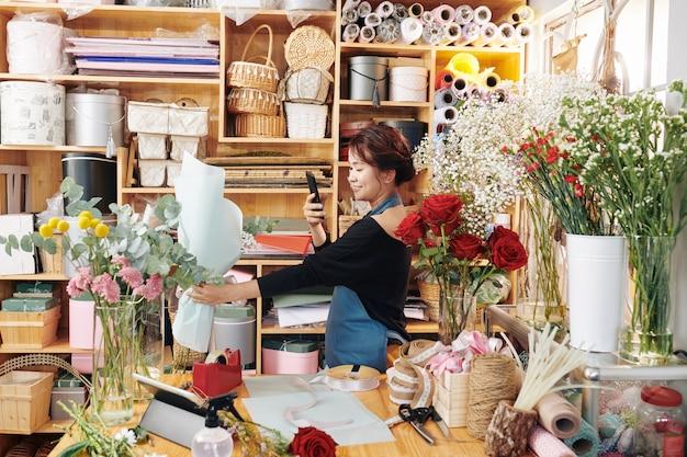 Floristin, die blumenstrauß in ihrem studio fotografiert